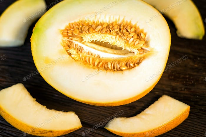 Fresh half of melon on wooden background, top view