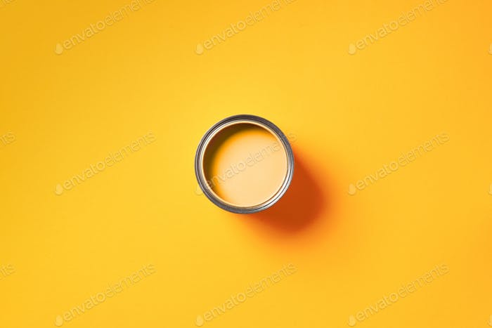 Open paint can with on trendy yellow background. Top view, copy space. Appartment renovation, repair