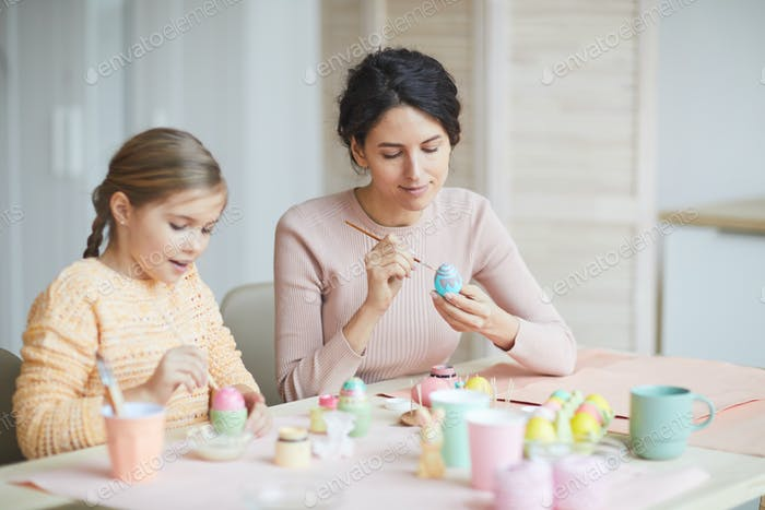 Young Mother Painting Easter Eggs at Home
