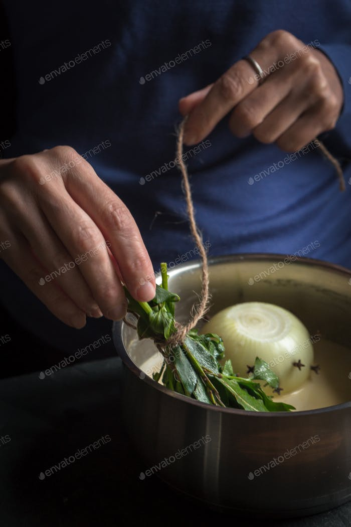 Preparation of bechamel sauce, onion and bouquet garnish in hands
