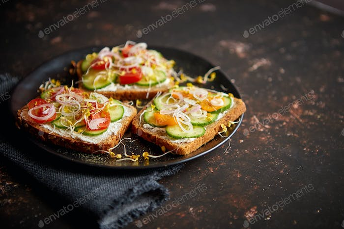Healthy toasts with cucomber, tomatoes and crumbled feta and radish sprouts