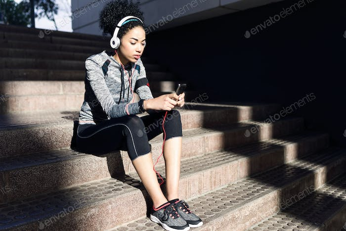 Fit and sporty young woman listening to music with mobile phone.