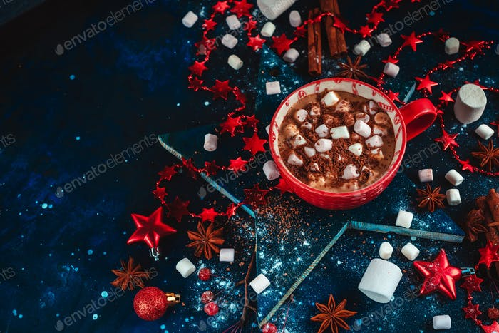 Hot cocoa winter flat lay. Red mug of Christmas chocolate on a star-shaped coaster with mini