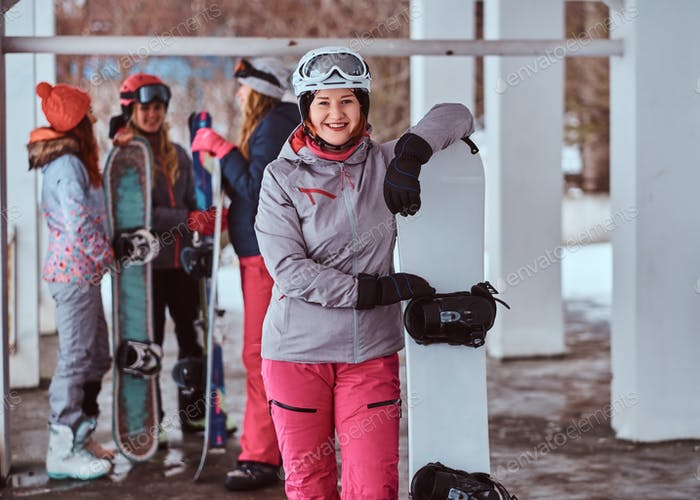 Redhead woman wearing winter sportswear posing with a snowboard