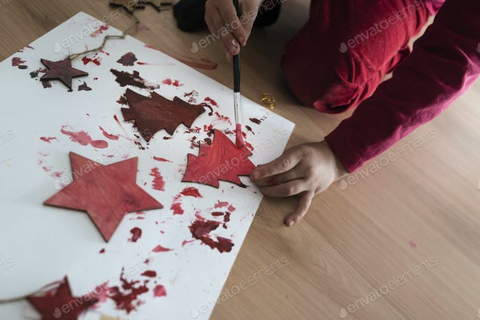 Young person painting wooden Christmas decorations