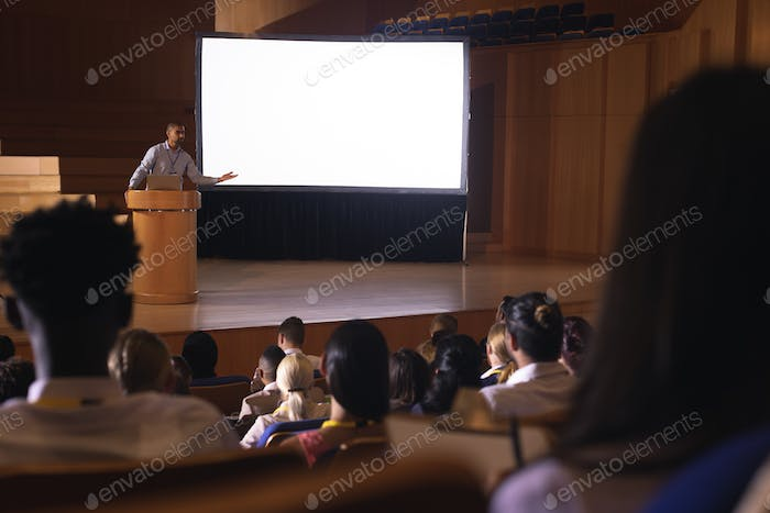 Businessman standing around podium and giving presentation in the auditorium