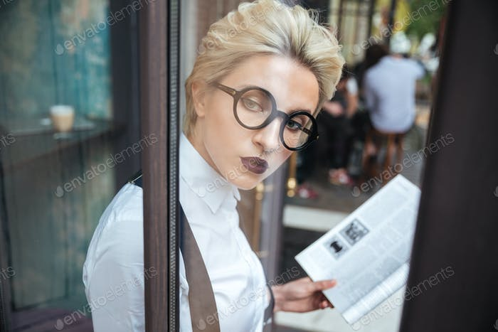 Beautiful young stylish woman reading book in cafe