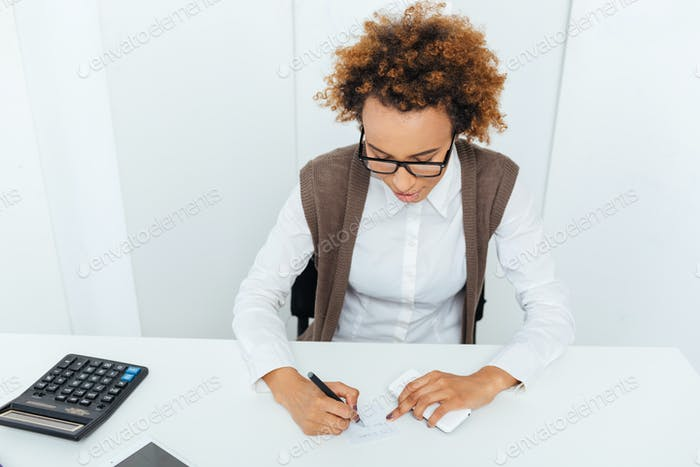 Thumbnail for Curly african young woman accountant sitting and writing in office