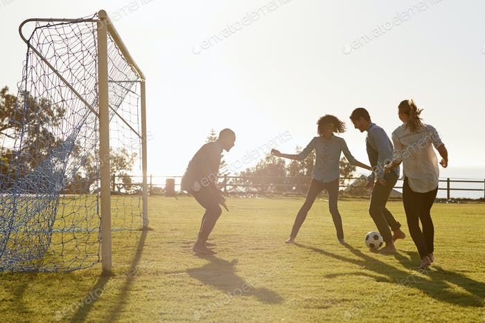 Young adults playing football in park one in goal, side view
