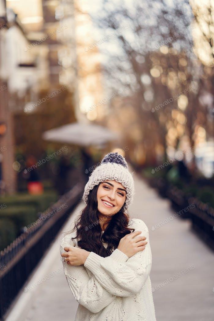 Niedlich Brünette in einem weißen Pullover in einer Stadt