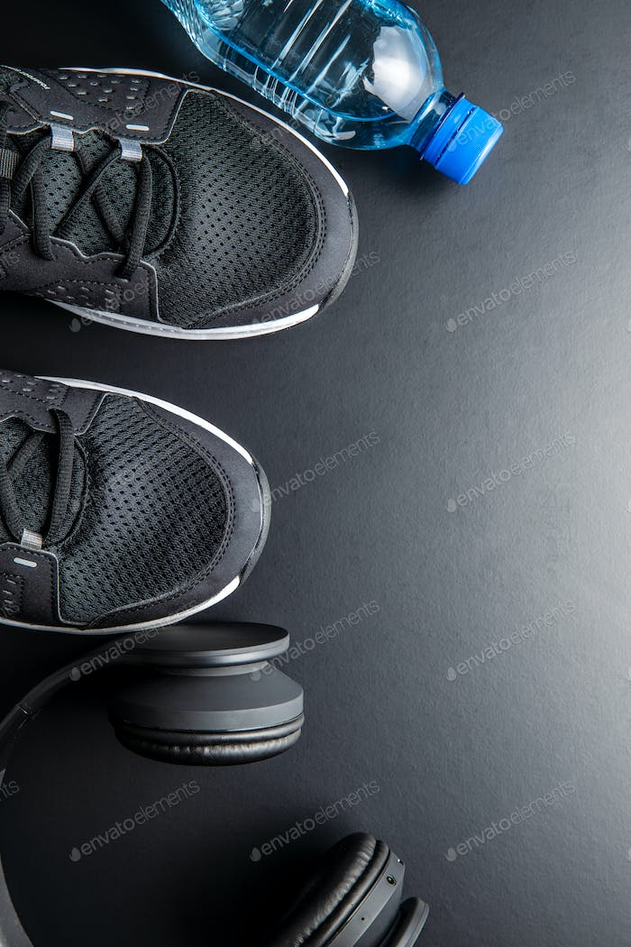 Fitness concept. Black sports shoes, headphones and bottle of water.