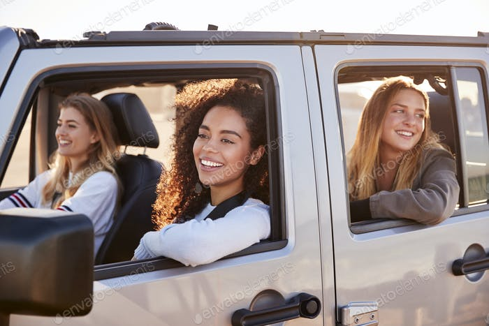 Young adult female friends going on vacation in a car