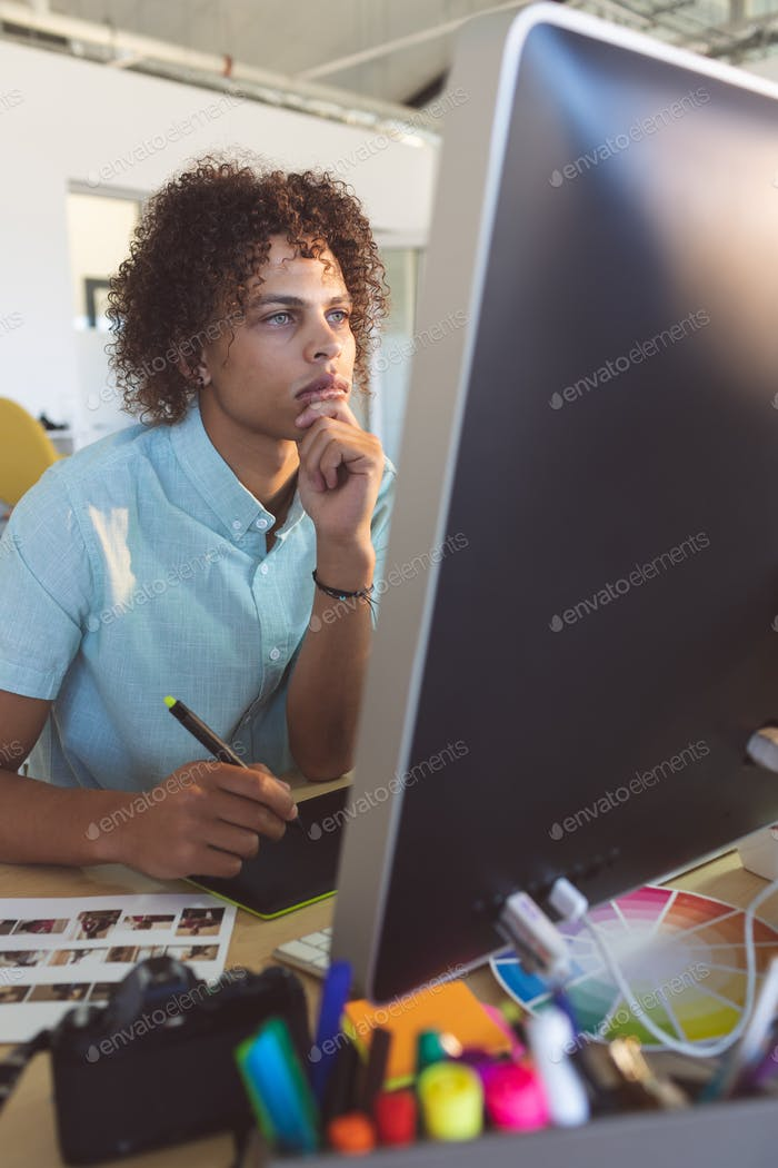 Young male graphic designer at computer screen while holding graphic pen at desk in office