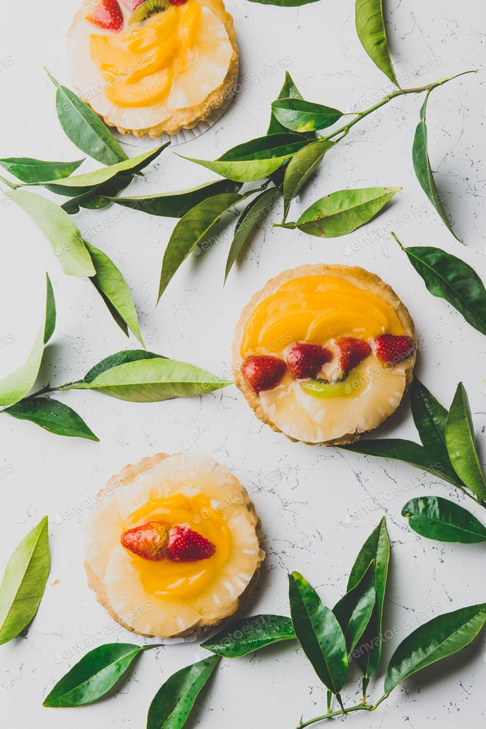 Flat lay of fruit and berry - pineaplle mango tarts and fresh leaves on white background