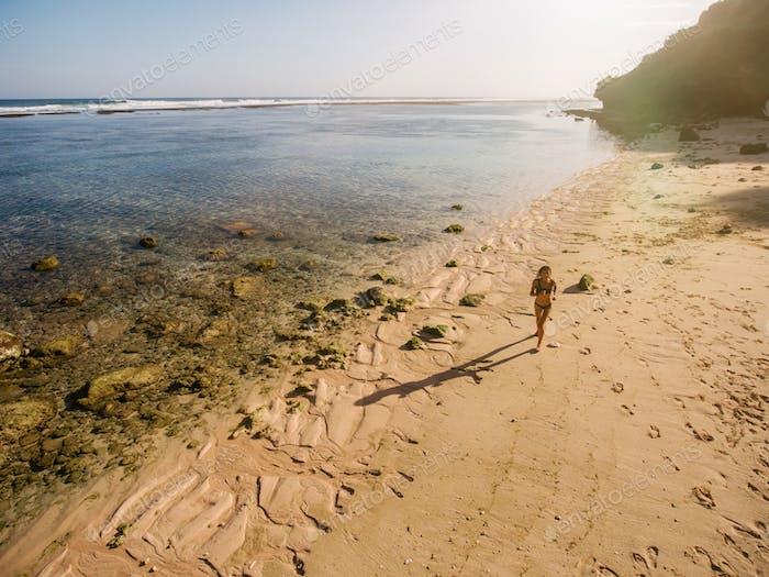 Tropischer Strand mit einer Frau läuft