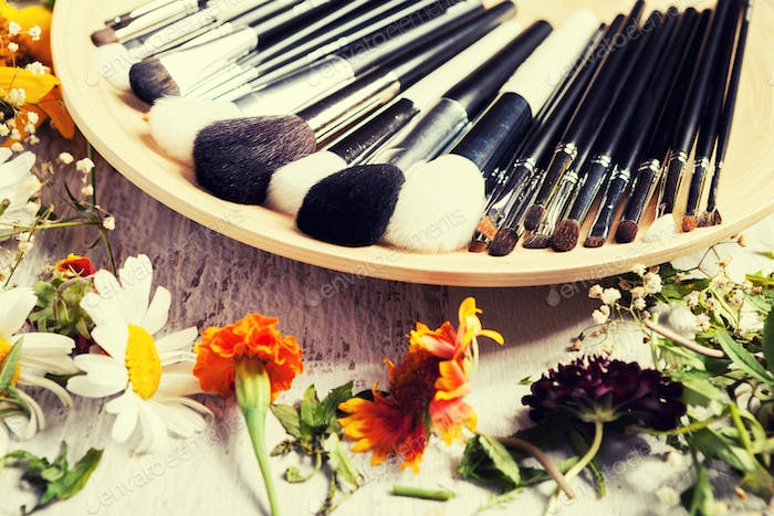Professional Make up brushes on plate next to wild flowers