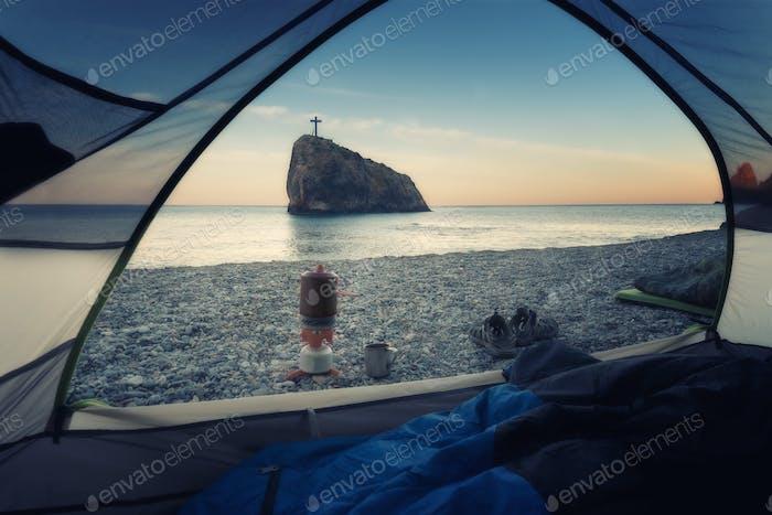 Ein Blick auf den Felsen des heiligen Phänomens vom Zelt am Strand in der Morgendämmerung. Krim