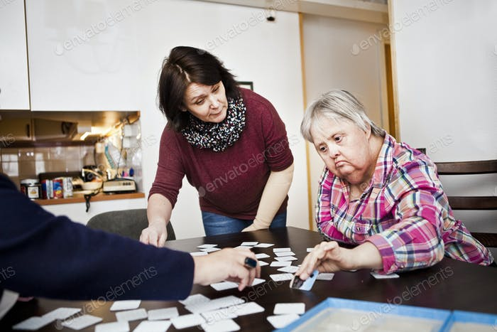 Healthcare worker assisting women with down syndrome in arranging cards at table
