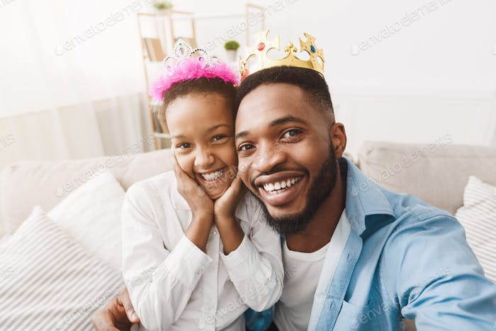 Joyful afro father and daughter wearing crowns and taking selfie