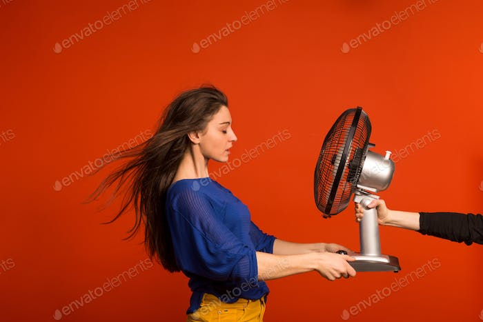 Portrait of a young beautiful woman with a fan in studio.
