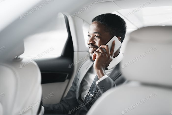 Happy afro businessman talking on cellphone in car