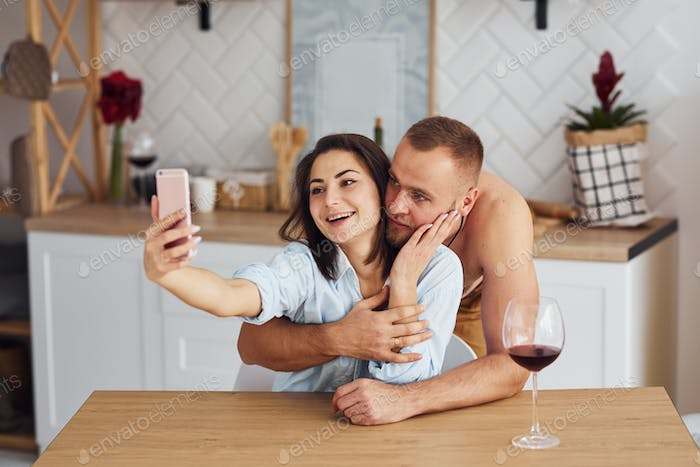 Couple together in the kitchen at morning time with mobile phone