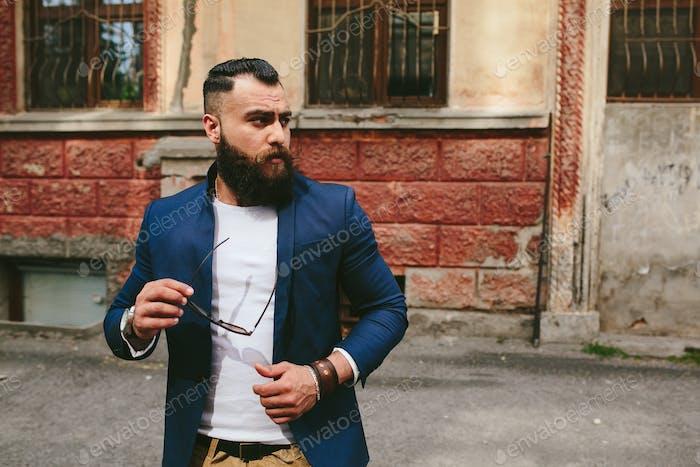 Стильный прохладный бородатый человек на фоне старого города