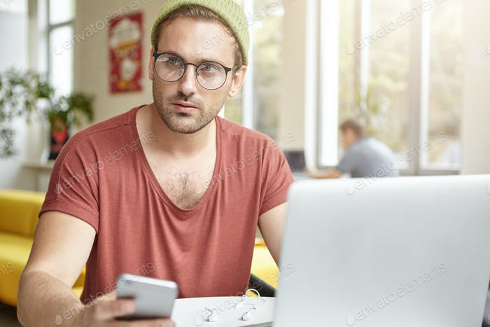 Fashionable man texts sms on smart phone to girlfriend, waits her in cafeteria or coffee shop, enjoy