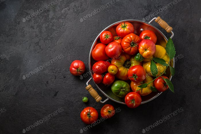Ripe tomatoes in a pan on black stone background, copy space