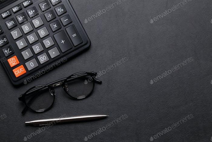 Schreibtischtisch mit Taschenrechner, Kugelschreiber und Gläsern