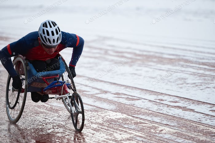Wheelchair racing. Physically impaired male athlete in helmet training