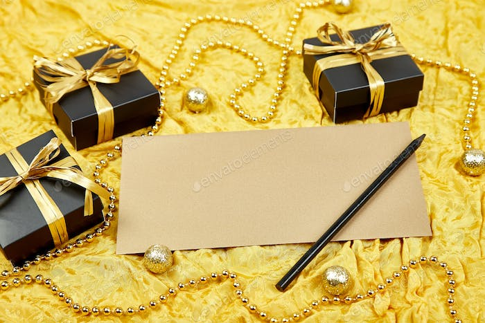 Black gift boxes with gold ribbon and  blank sheet paper