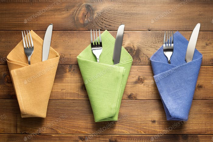 knife and fork in napkin on wood