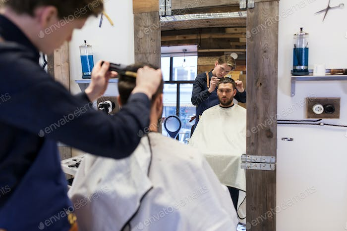 man and barber cutting hair at barbershop
