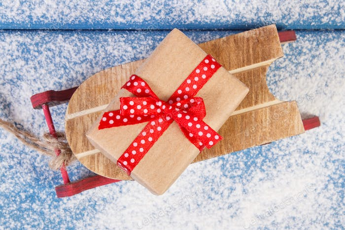 Wooden sled and wrapped gift with ribbons for Christmas or other celebration