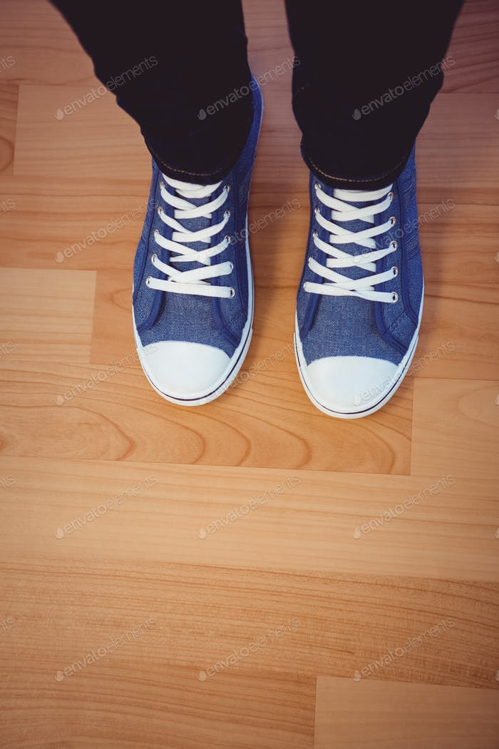 Cropped image of woman wearing sneakers against wooden plank