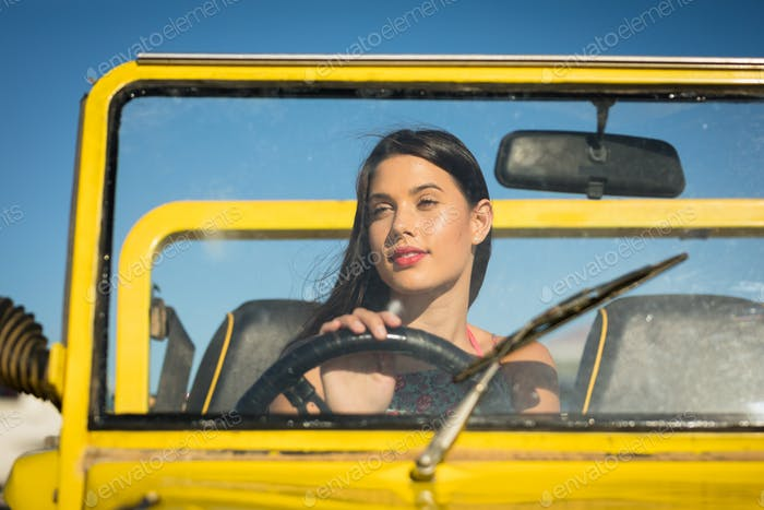 Happy caucasian woman sitting in beach buggy by the sea
