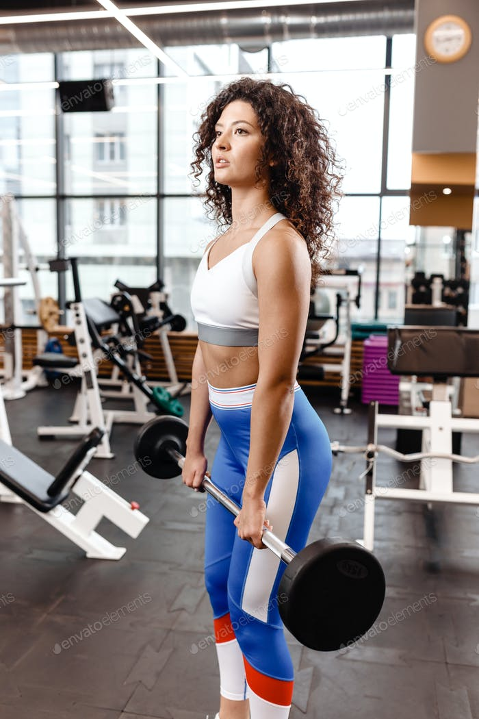 Good fit curly girl dressed in sports clothes is doing deadlift with barbell in the modern gym full