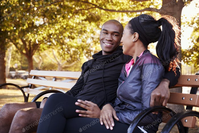 Young black couple sitting on bench in Brooklyn park