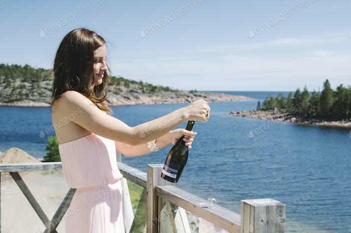Mujer joven que abre botella de vino en el balcón