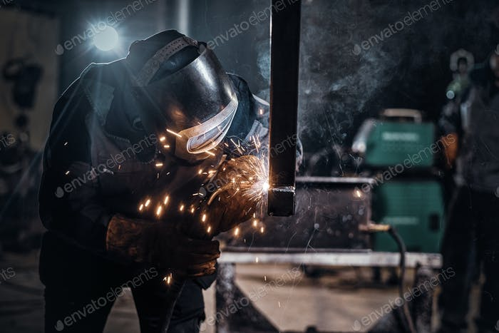 Man is working at the busy metal factory