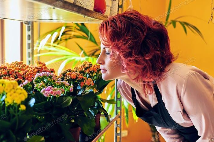 Rothaarige weibliche Blick auf Blumen