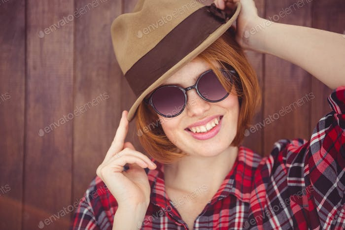 smiling hipster woman  wearing a trilby and sunglasses against a wooden background
