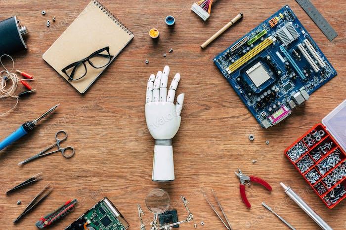 Draufsicht der Armprothese auf Holztisch mit Werkzeugen, Brillen und Lehrbuch