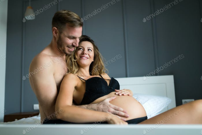 Happy pregnant woman enjoying with husband in bedroom