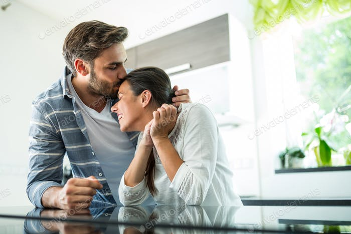 Man kissing on woman forehead