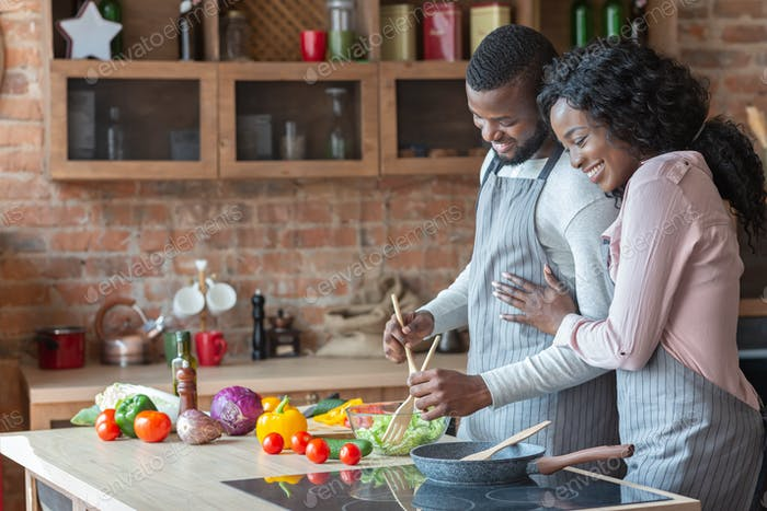 Cheerful black family cooking dinner together in kitchen