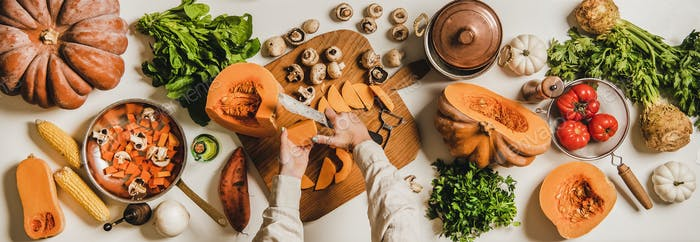 Female hands cooking over white table with healthy autumn products