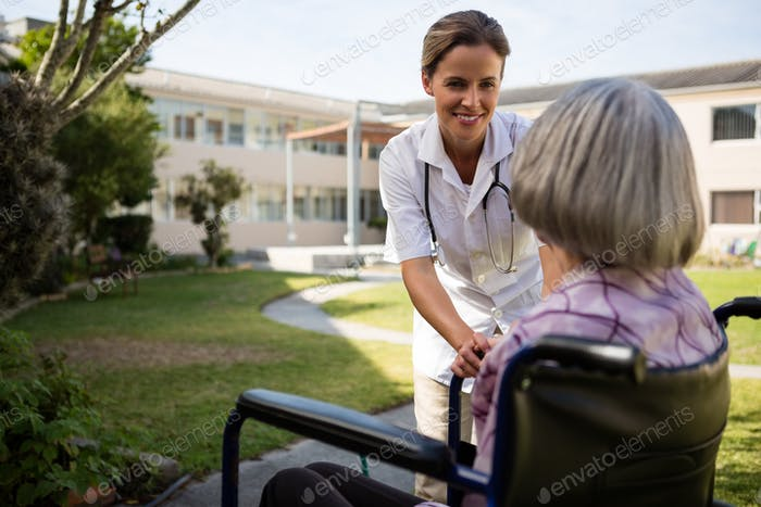 Doctor talking to senior woman sitting on wheelchair