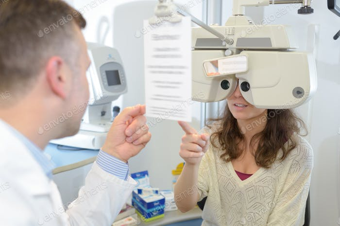 male optometrist examining young patient on phoropter